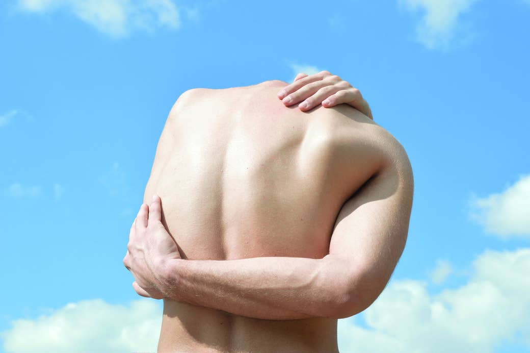 A man wraps his arms around his back in front of a blue sky