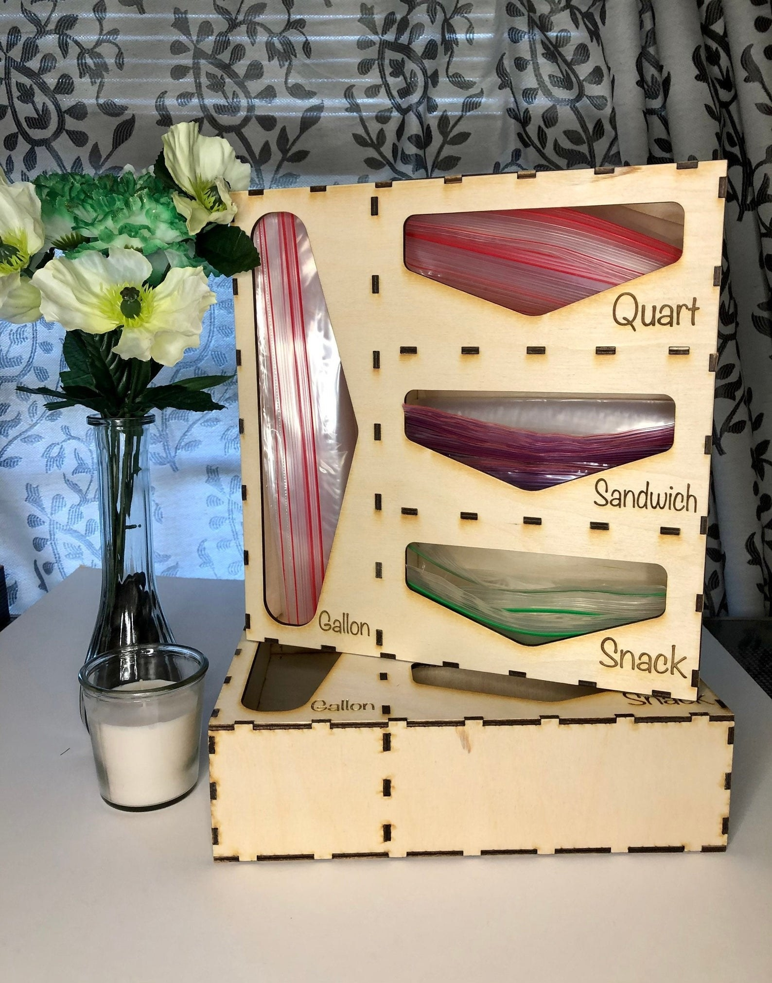 wooden organizer with slots for ziploc bags with the words quart, sandwich, snack, and gallon on it