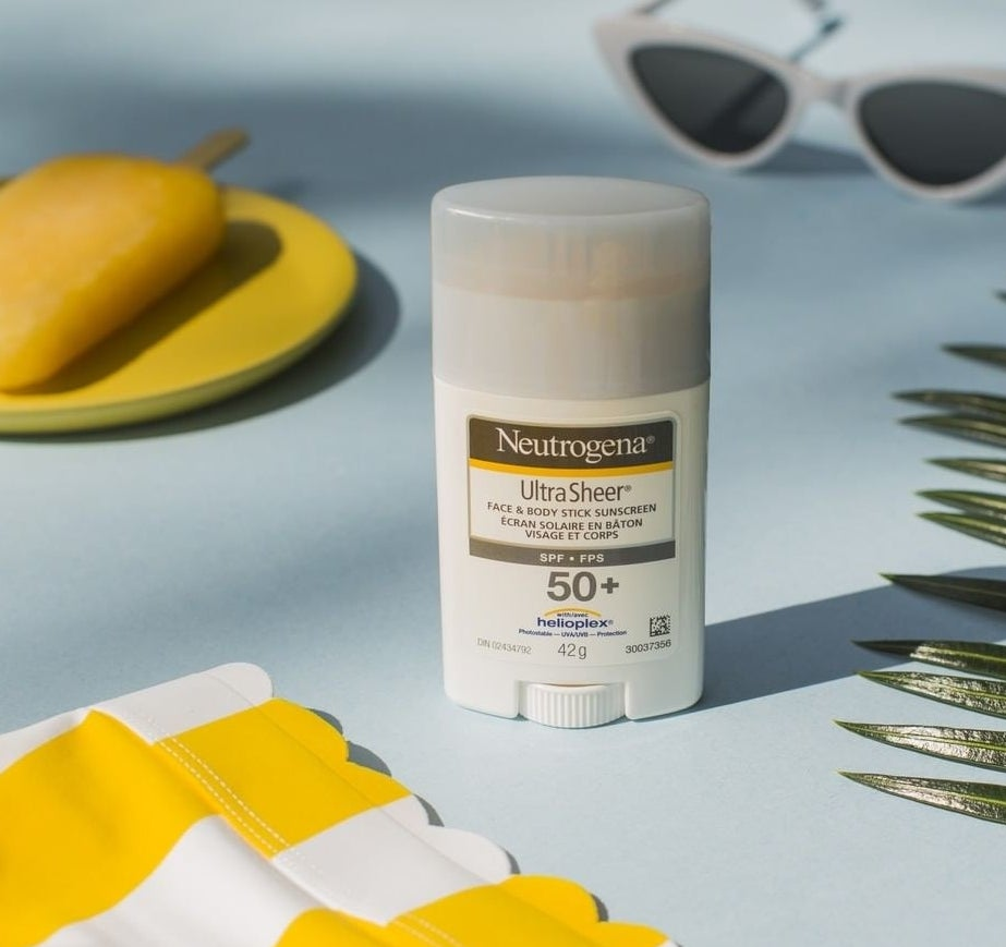 A stick of Neutrogena sunscreen on a table surrounded by sunglasses, a leaf, and a tablecloth