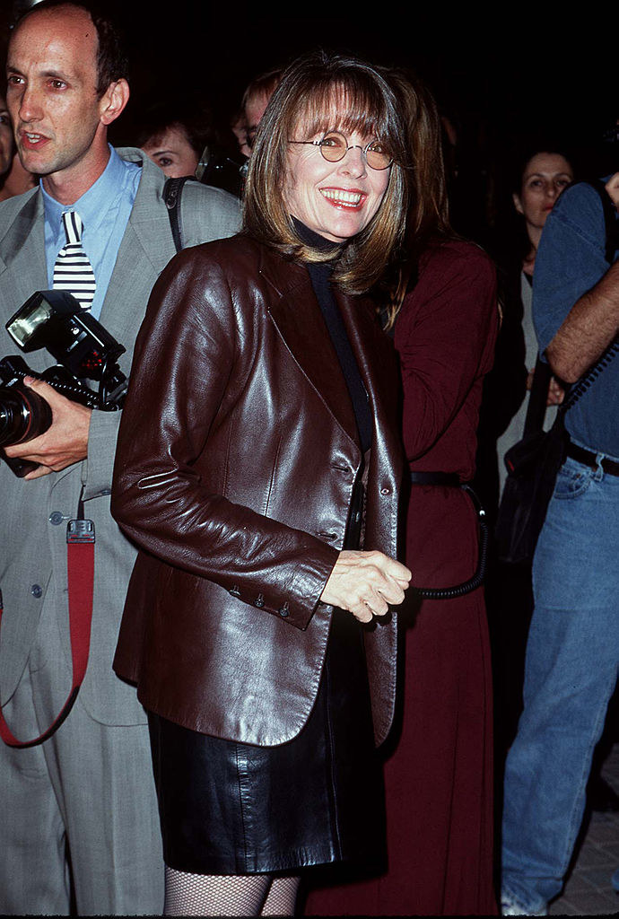 smiling in a turtleneck and a leather skirt