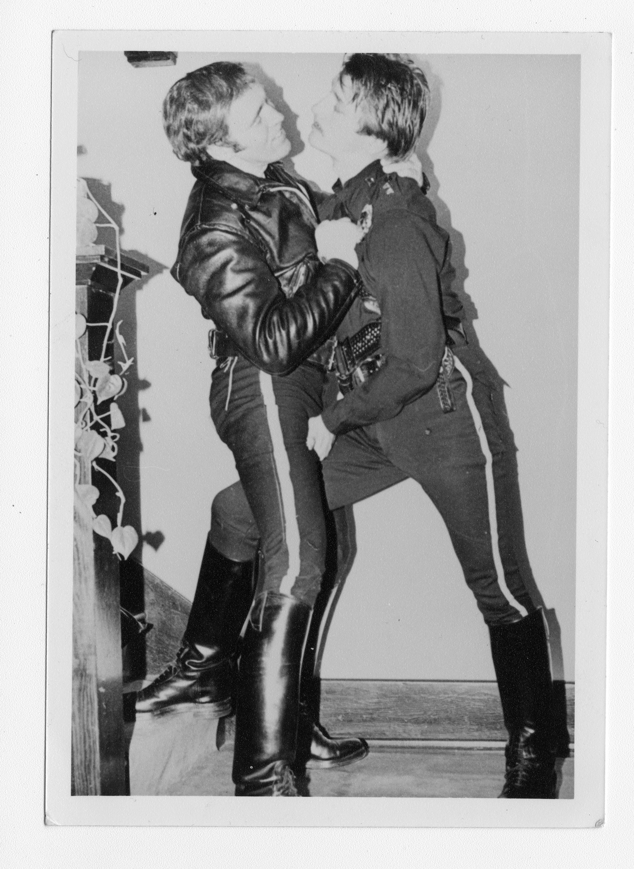 Two men wearing militaristic leather uniforms hold one another as one grabs the other's crotch