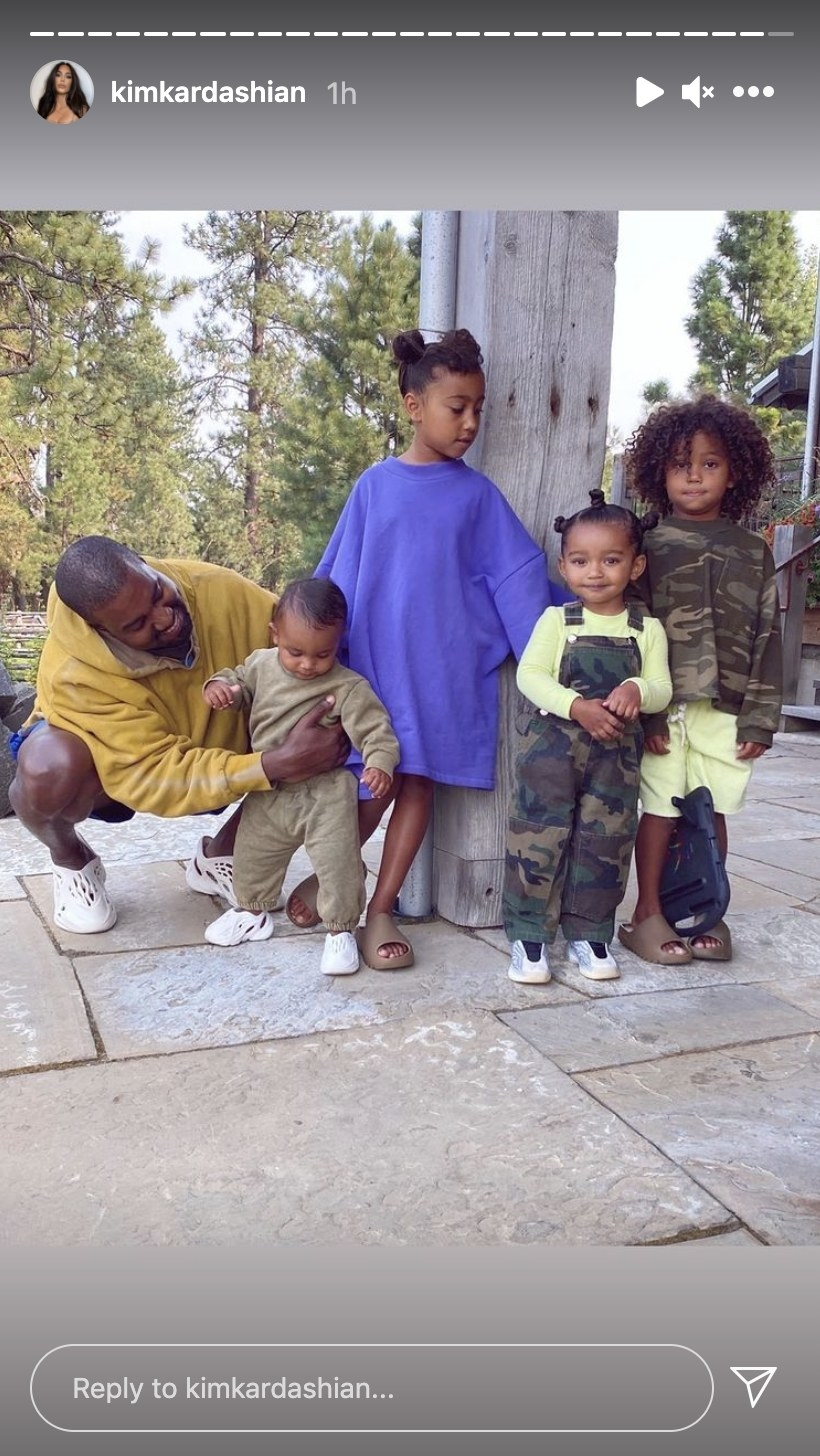 Kanye poses with the couple's children helping Psalm stand with his siblings