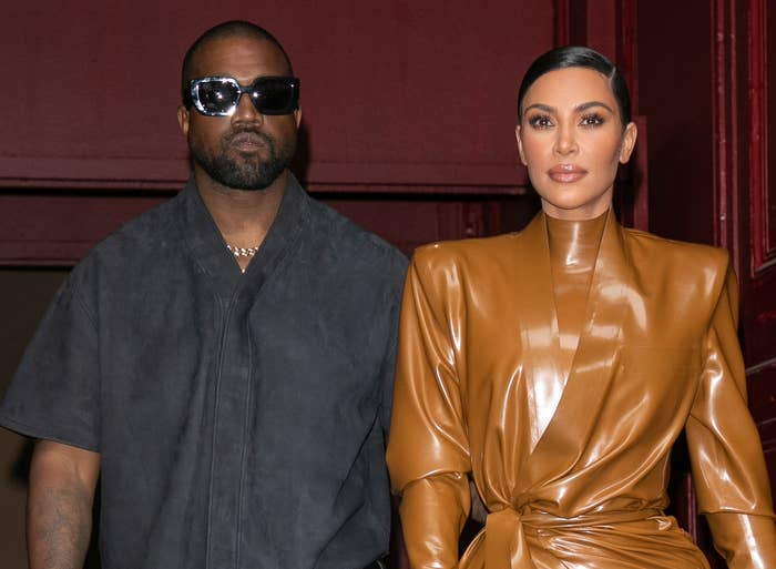 Kim and Kanye walk arm in arm while leaving a building