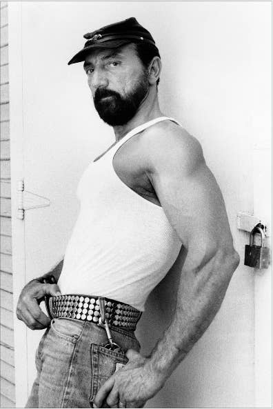 A bearded white man in jeans and a tank top leans against a door