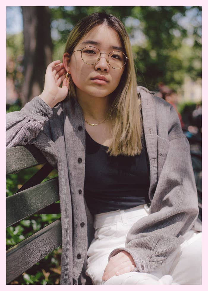 A woman in glasses and an oversized shirt sitting on a park bench looking at the camera