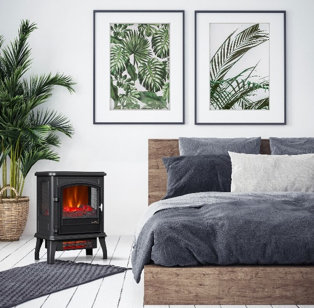 The electric fireplace creating a warm, cozy atmosphere in the bedroom