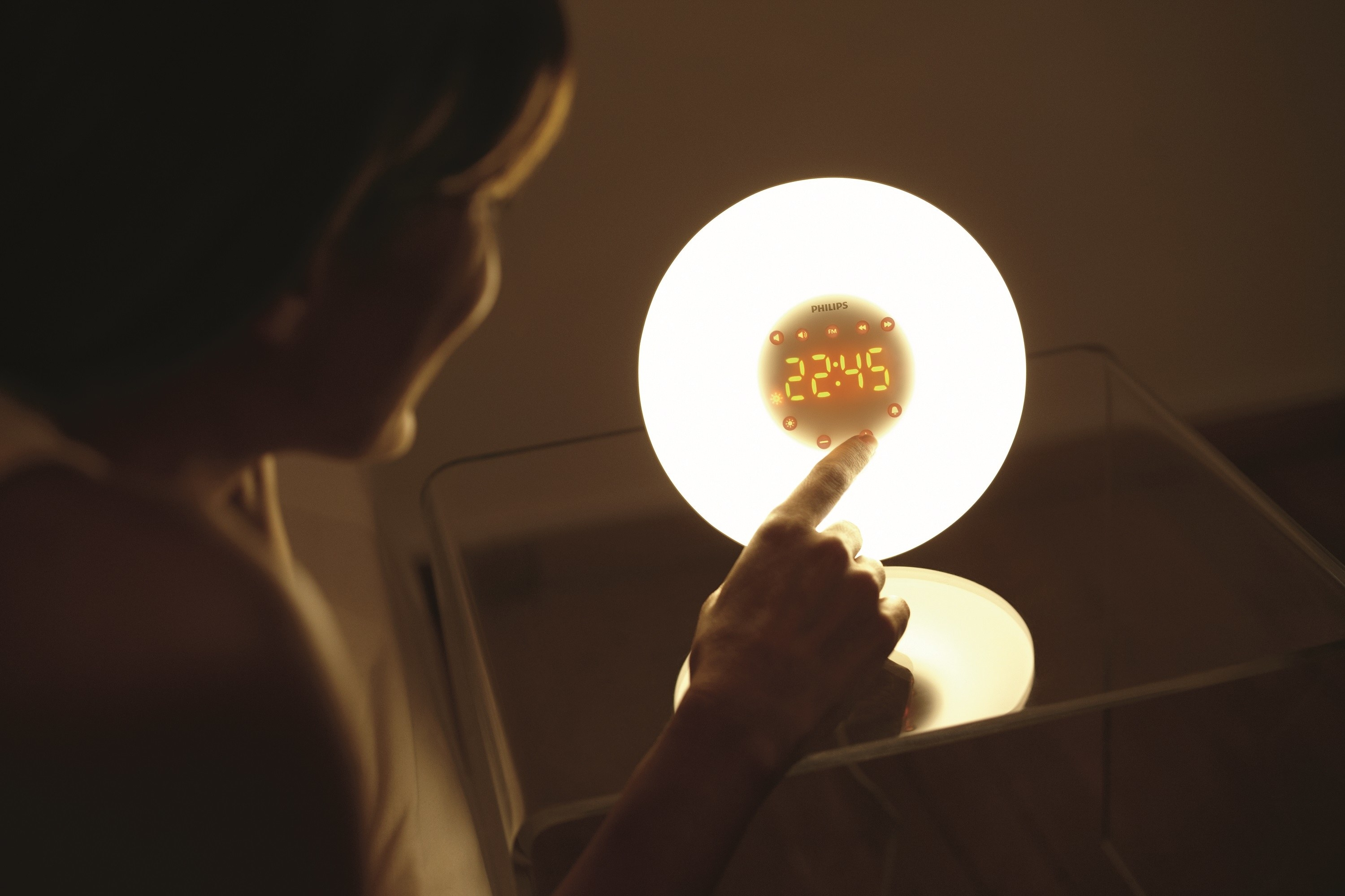 An LED lit alarm clock that gives off a warm, natural lighting on a stand