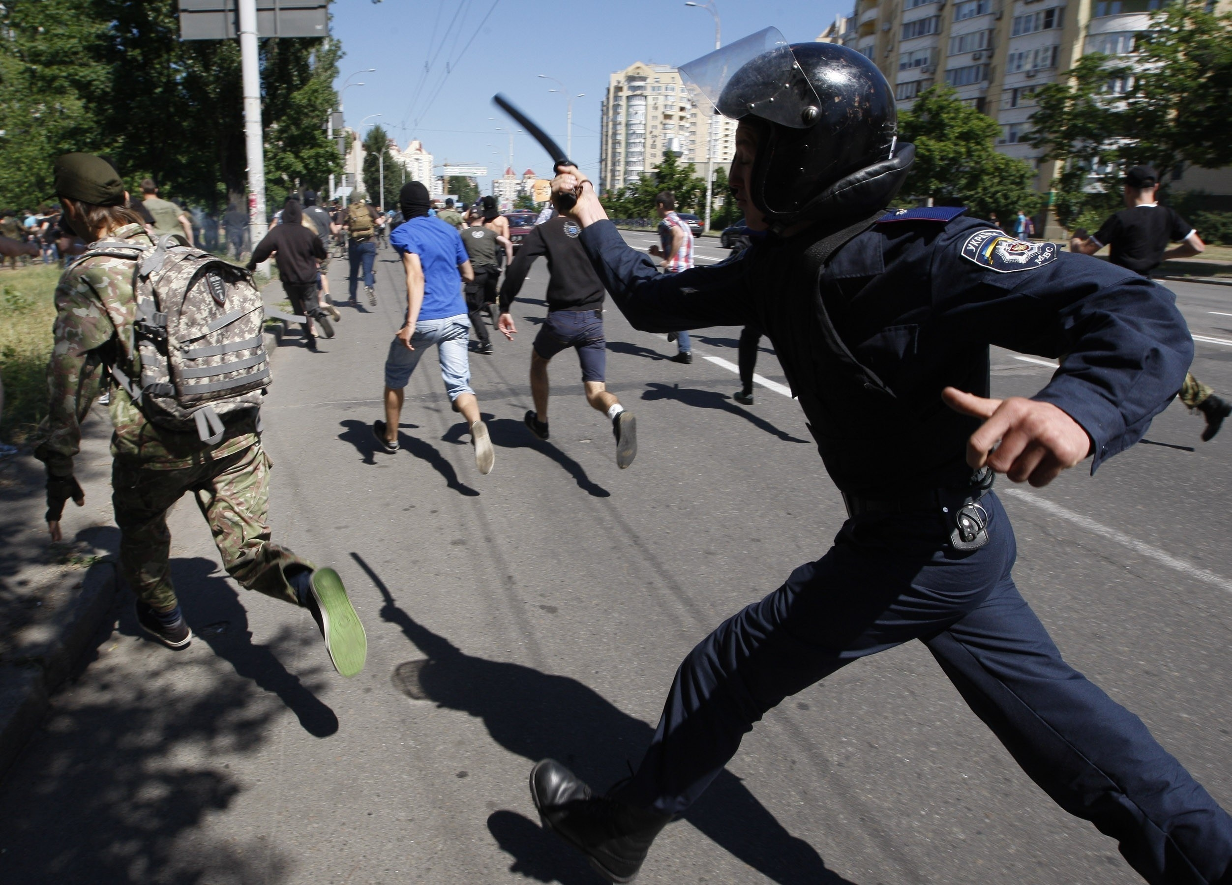 A police officer holding a baton runs after protesters