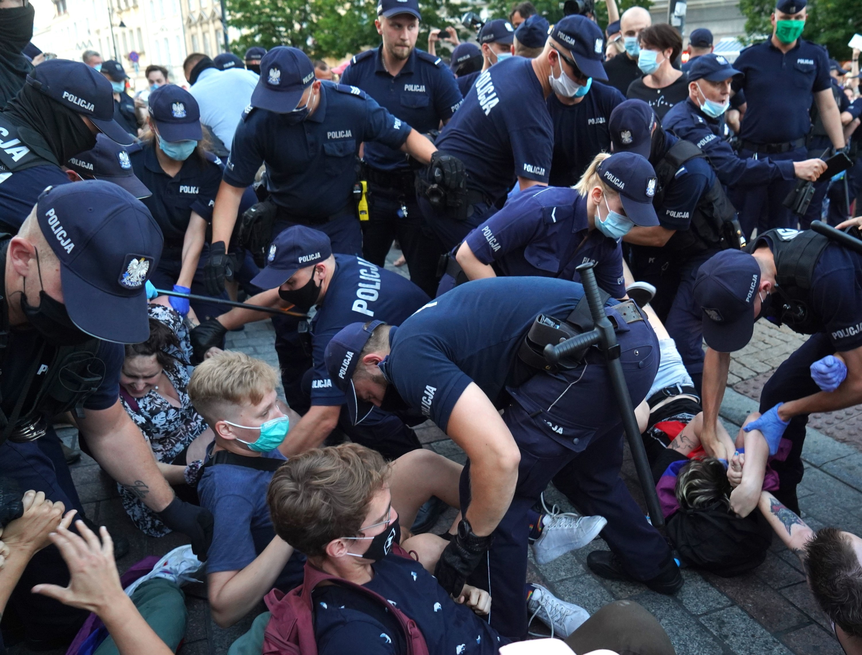 Officers surround and try to remove protesters sitting and lying on the ground