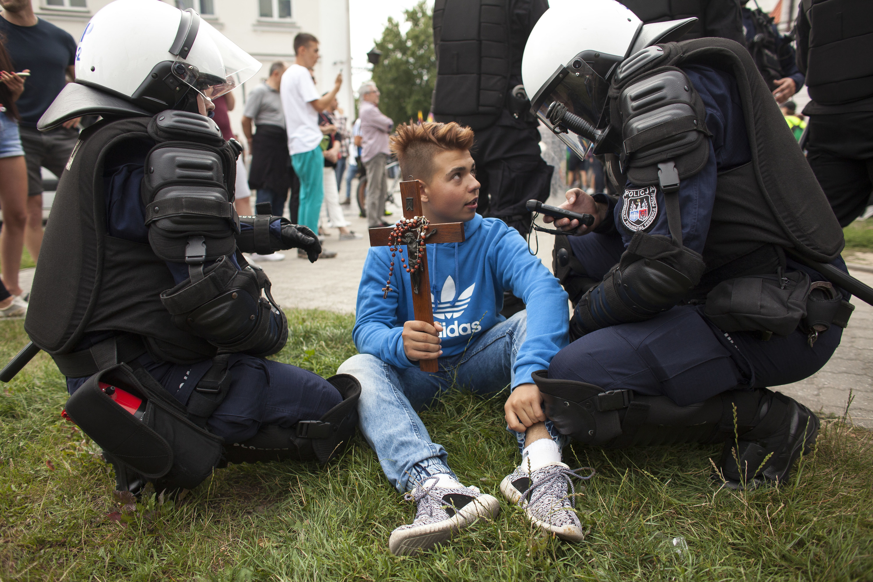 Officers kneel next to a kid holding a crucifix