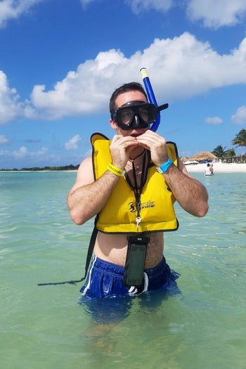 reviewer with the black waterproof case around neck while in the water