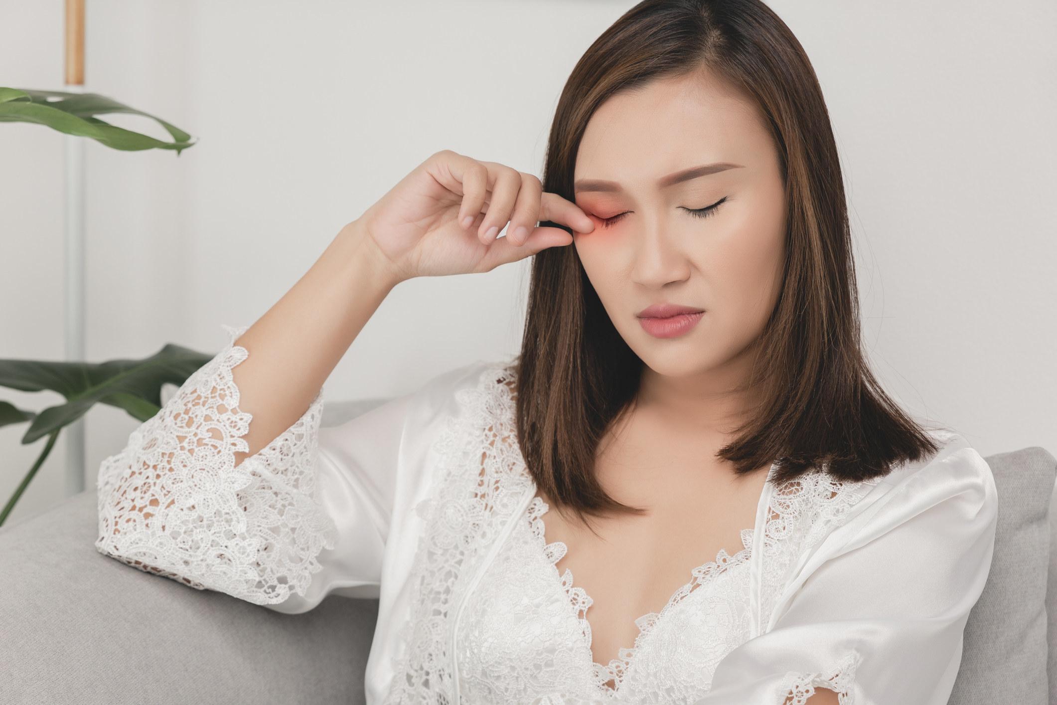 Woman rubbing her dry eye