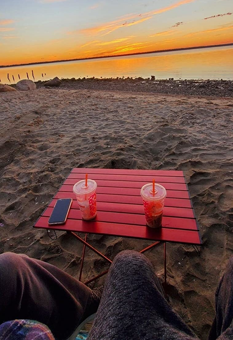 reviewer photo of a beach table in the sand with a sunset in the background