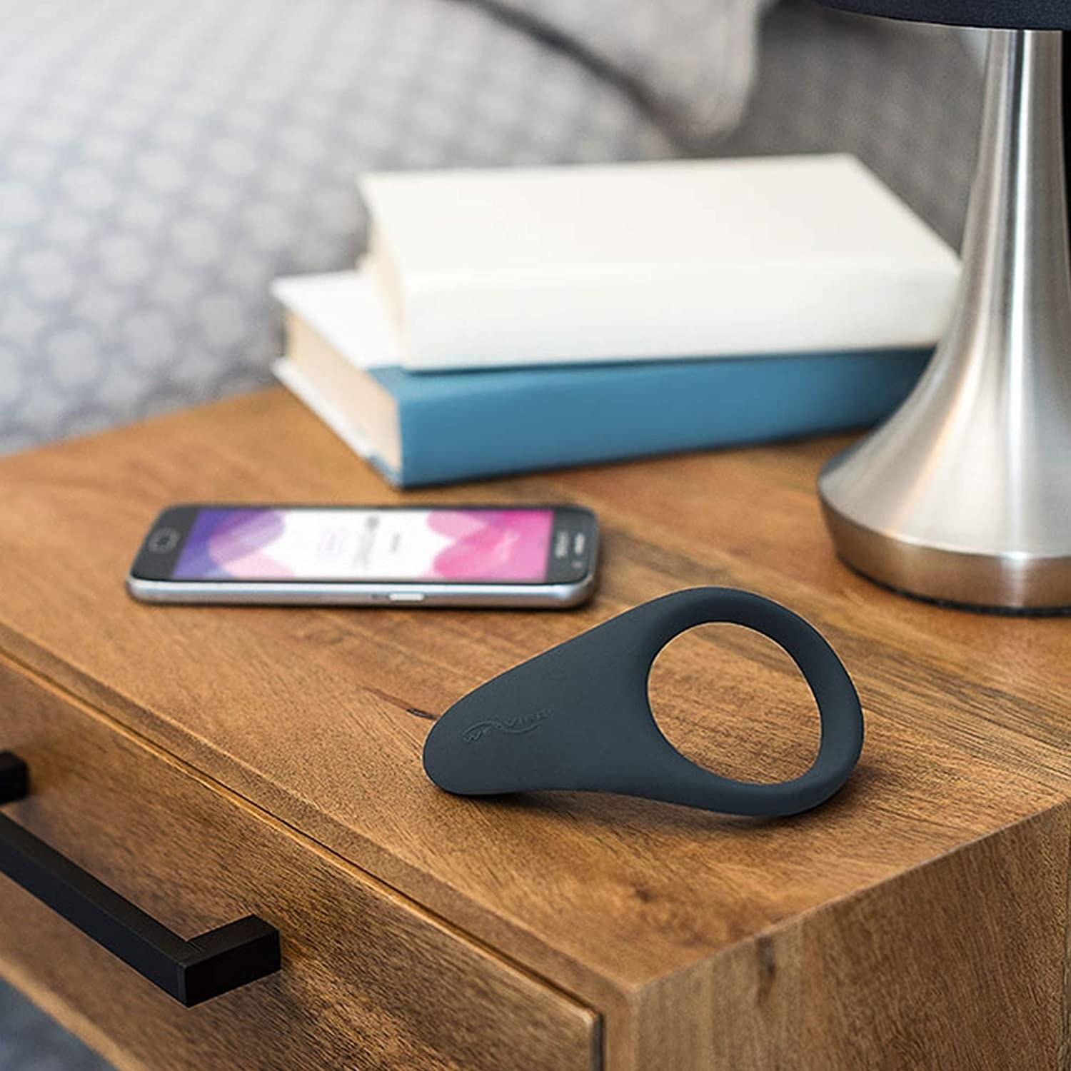the cock ring on a bedside table with books and a smartphone displaying the app