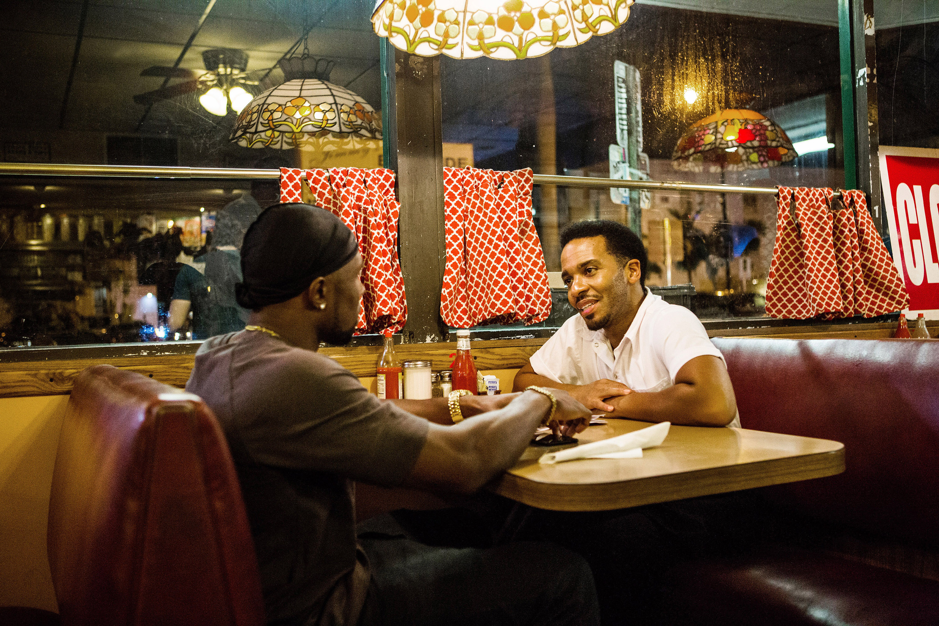 Trevante Rhodes sits across from Andre Holland in a diner