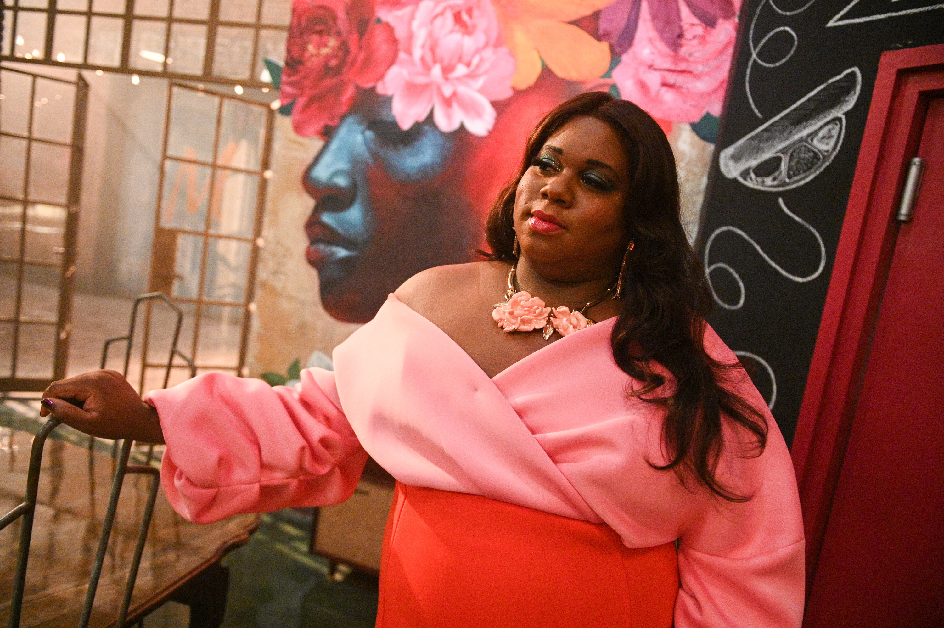 Alex Newell stands in a gorgeous pink dress