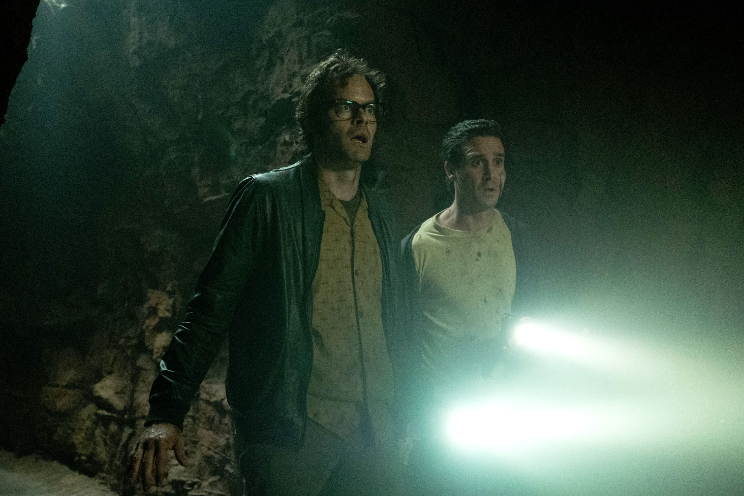 Bill Hader and James Ransone in a cave with flashlights