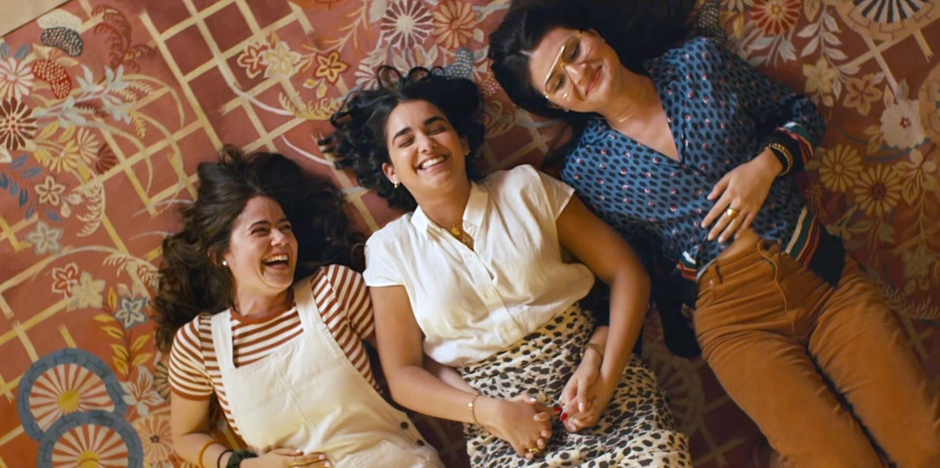 Molly Gordon, Geraldine Viswanathan, and Phillipa Soo laughing on the fllor