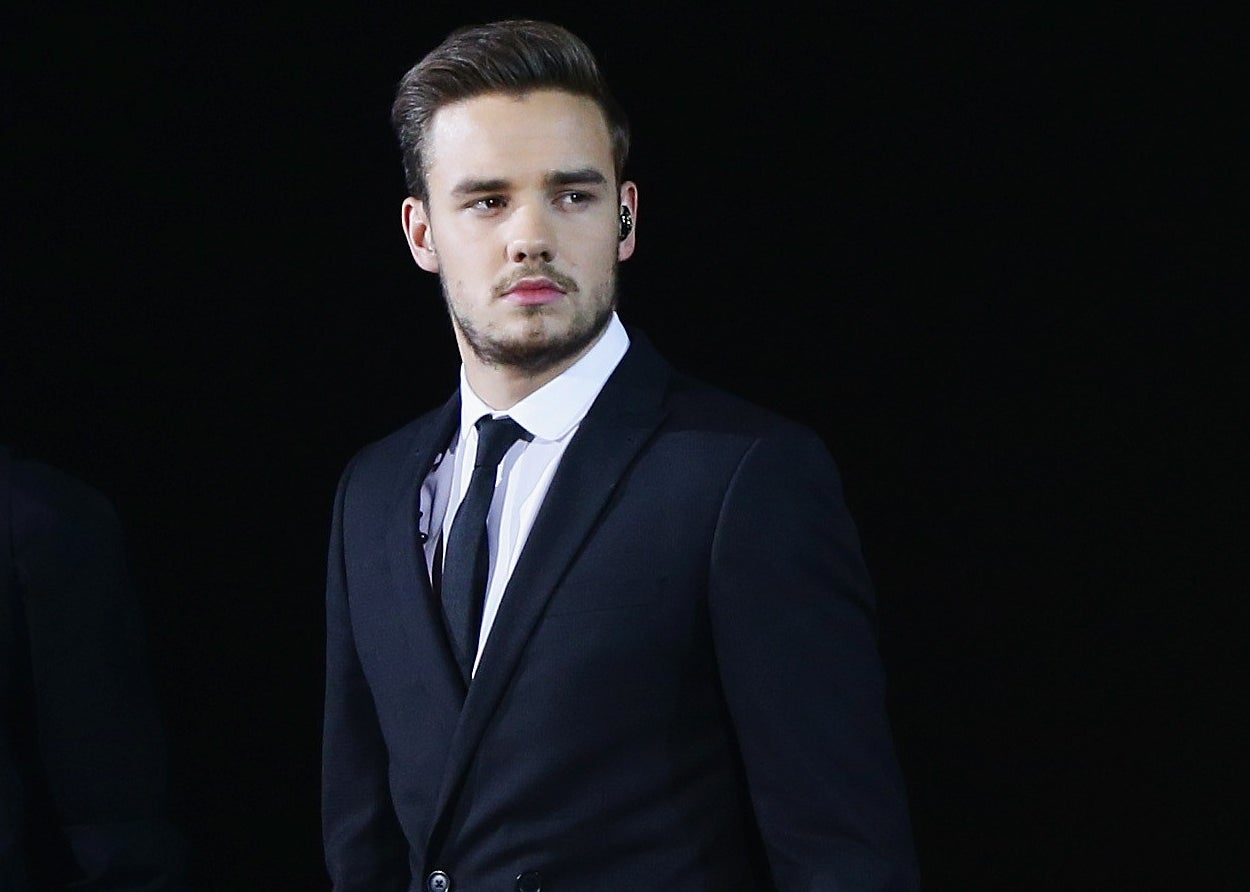 Liam wears a suit and looks serious onstage