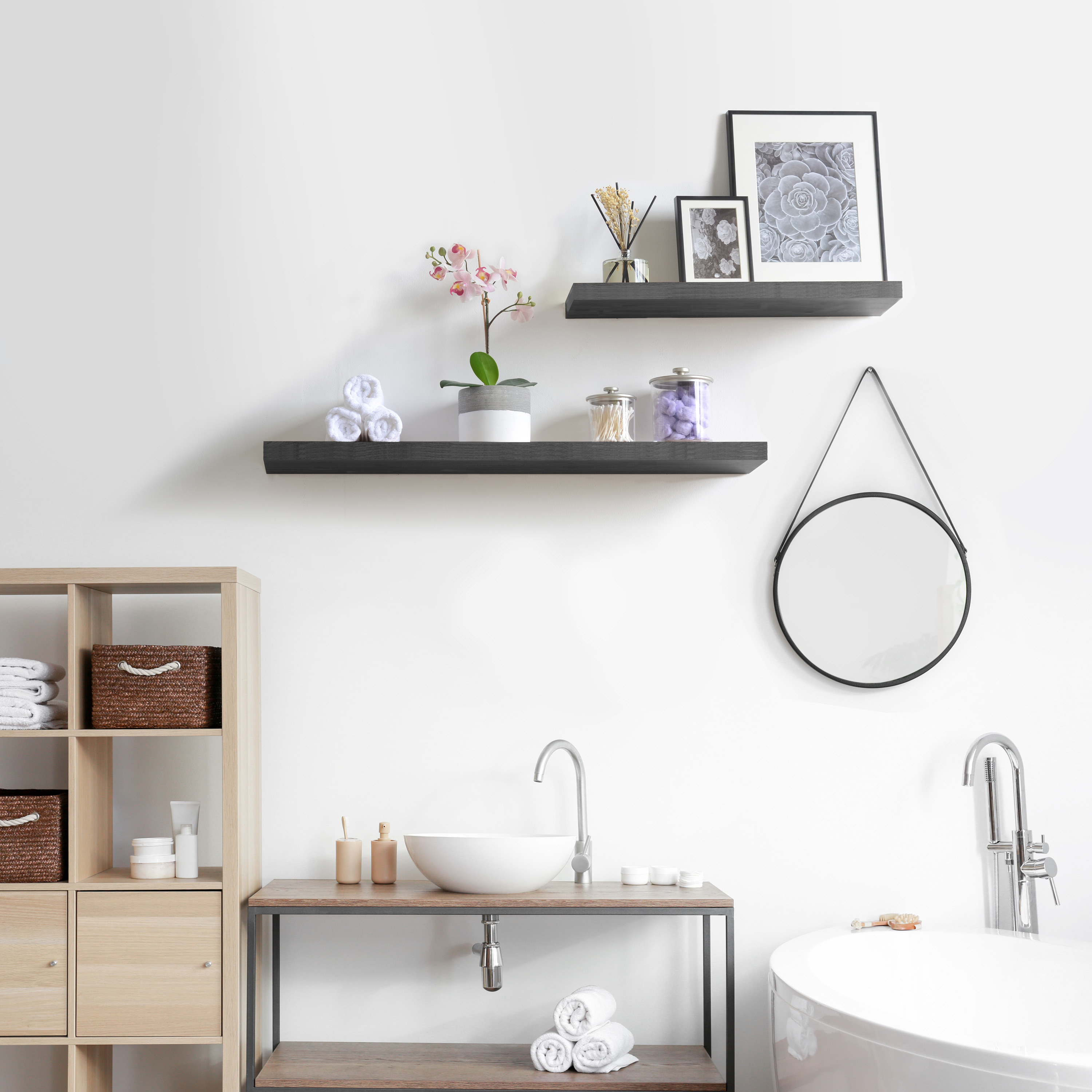 two floating black shelves with photos and faux plants