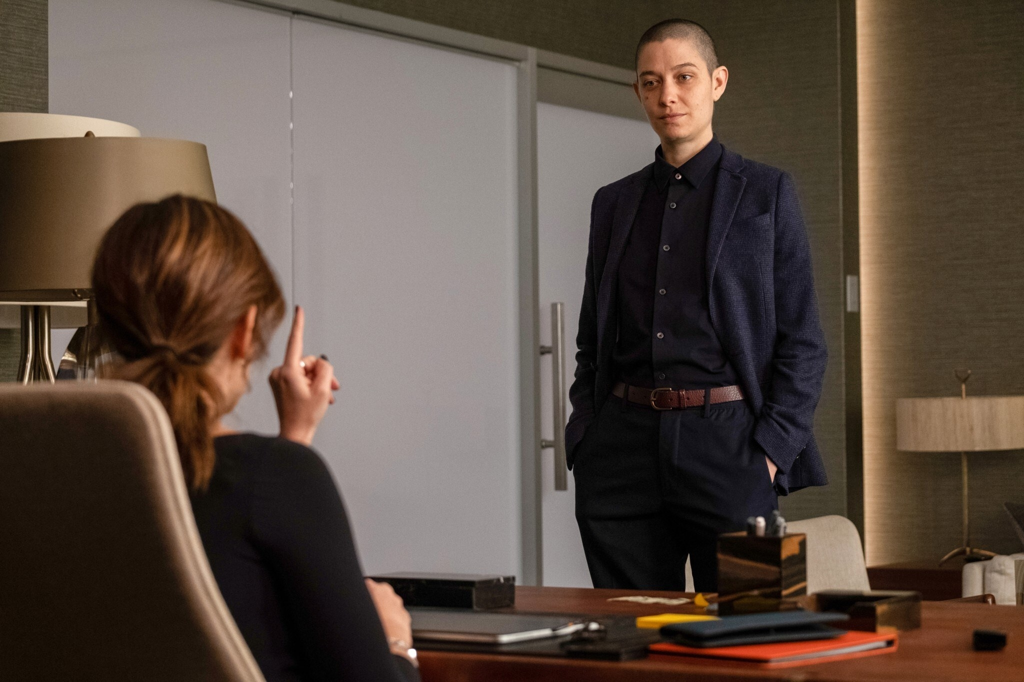 Asia Kate Dillon stands in front of Maggie Siff's desk