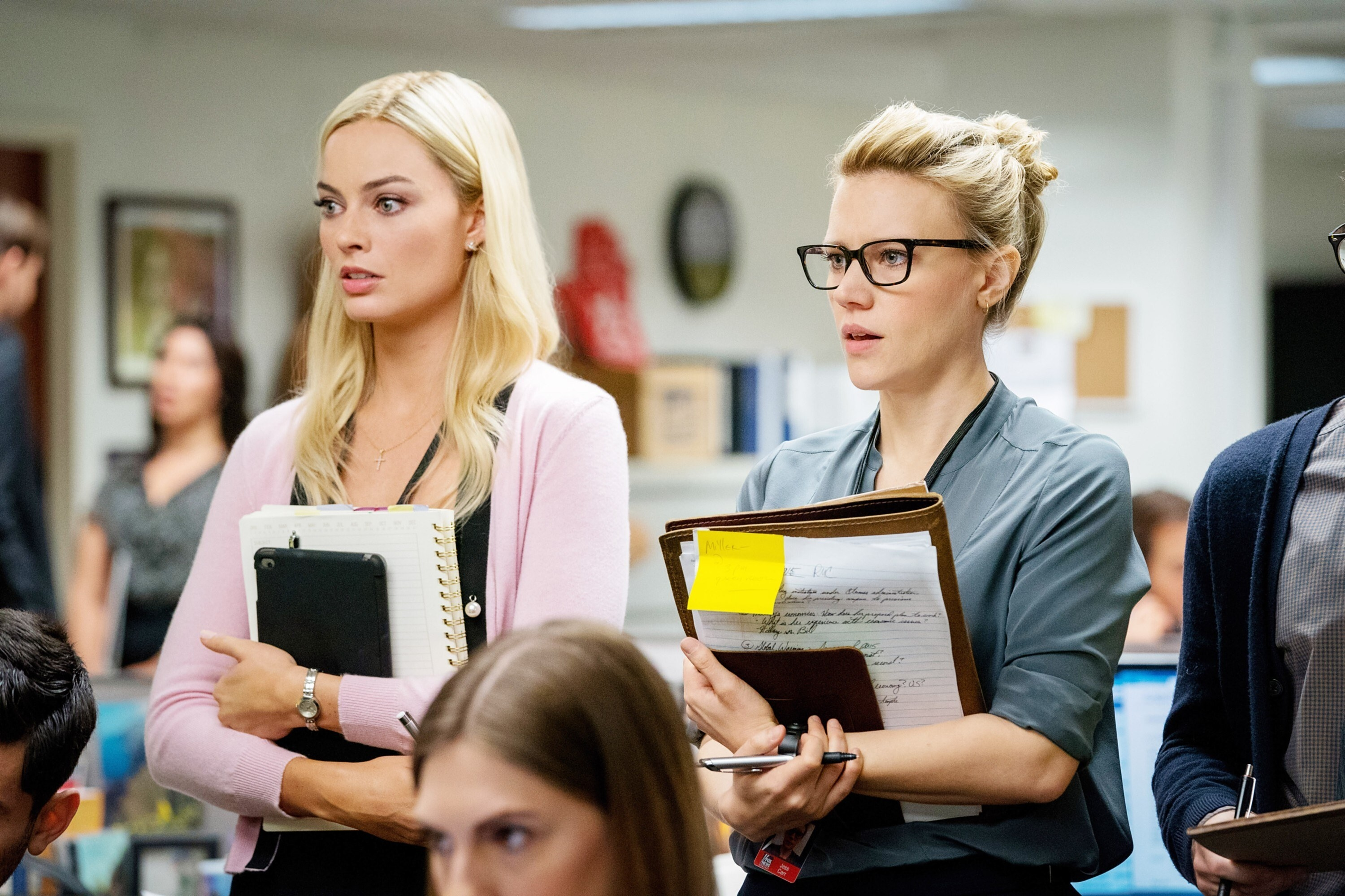Margot Robbie and Kate McKinnon stand in a press room with notebooks
