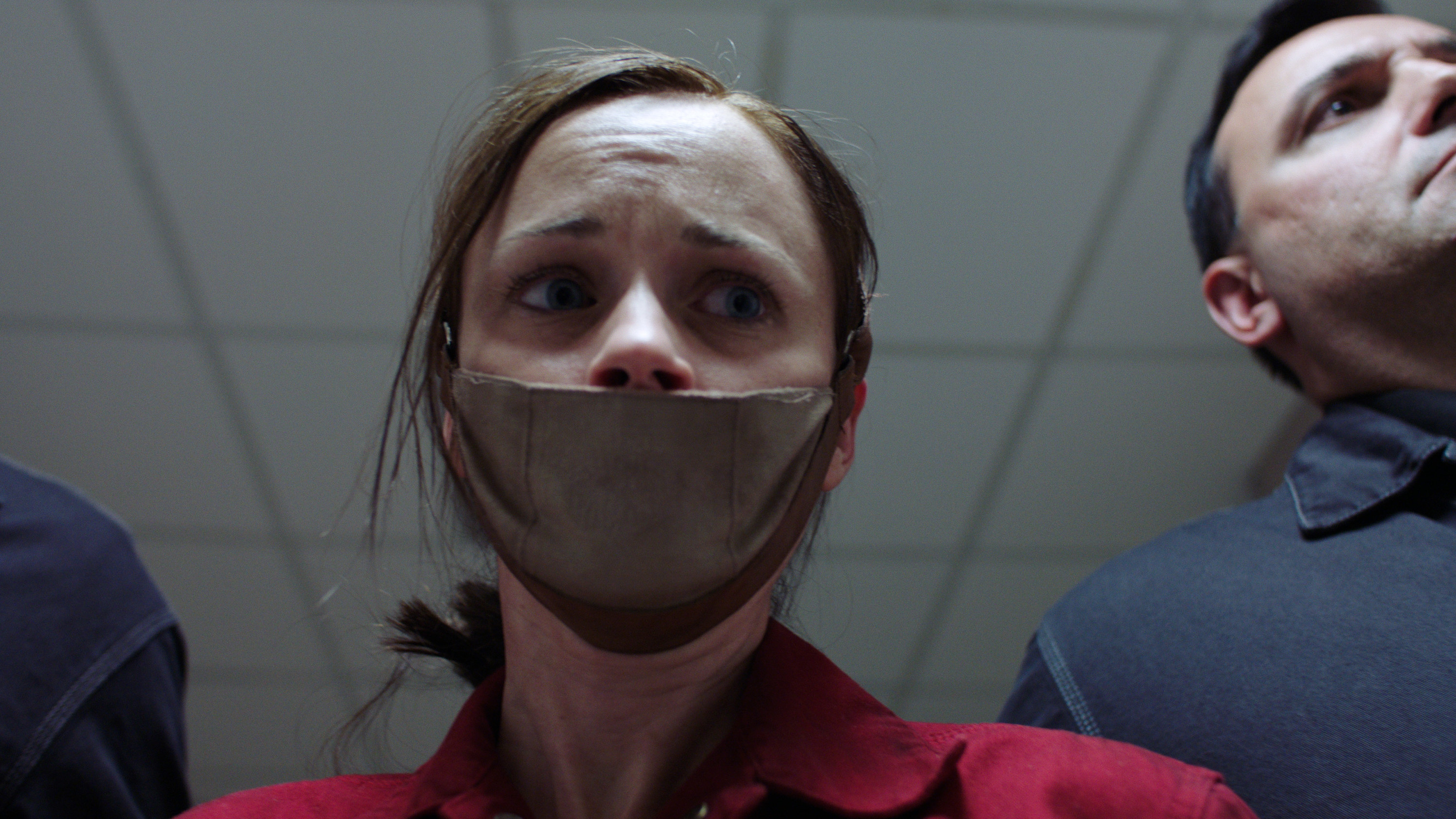 Alexis Bledel being led down a hallway by guards with a mask over her mouth