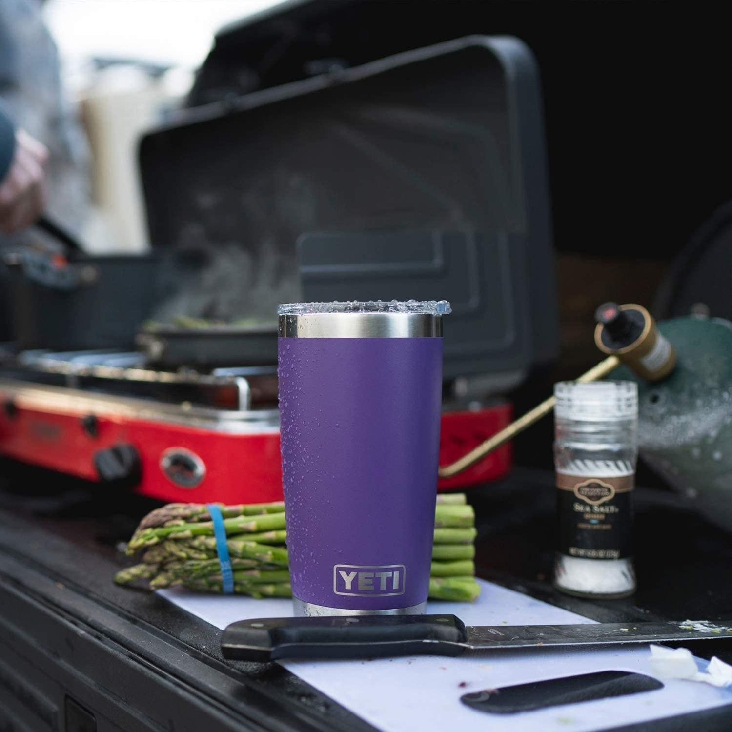 the purple yeti rambler on a grill next to asparagus
