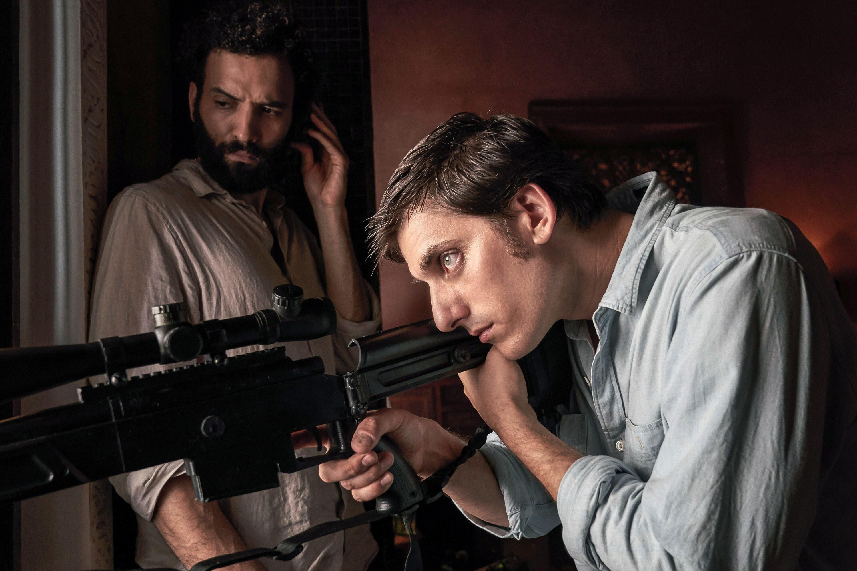 Luca Marinelli aims a gun out a window while Marwan Kenzari looks on