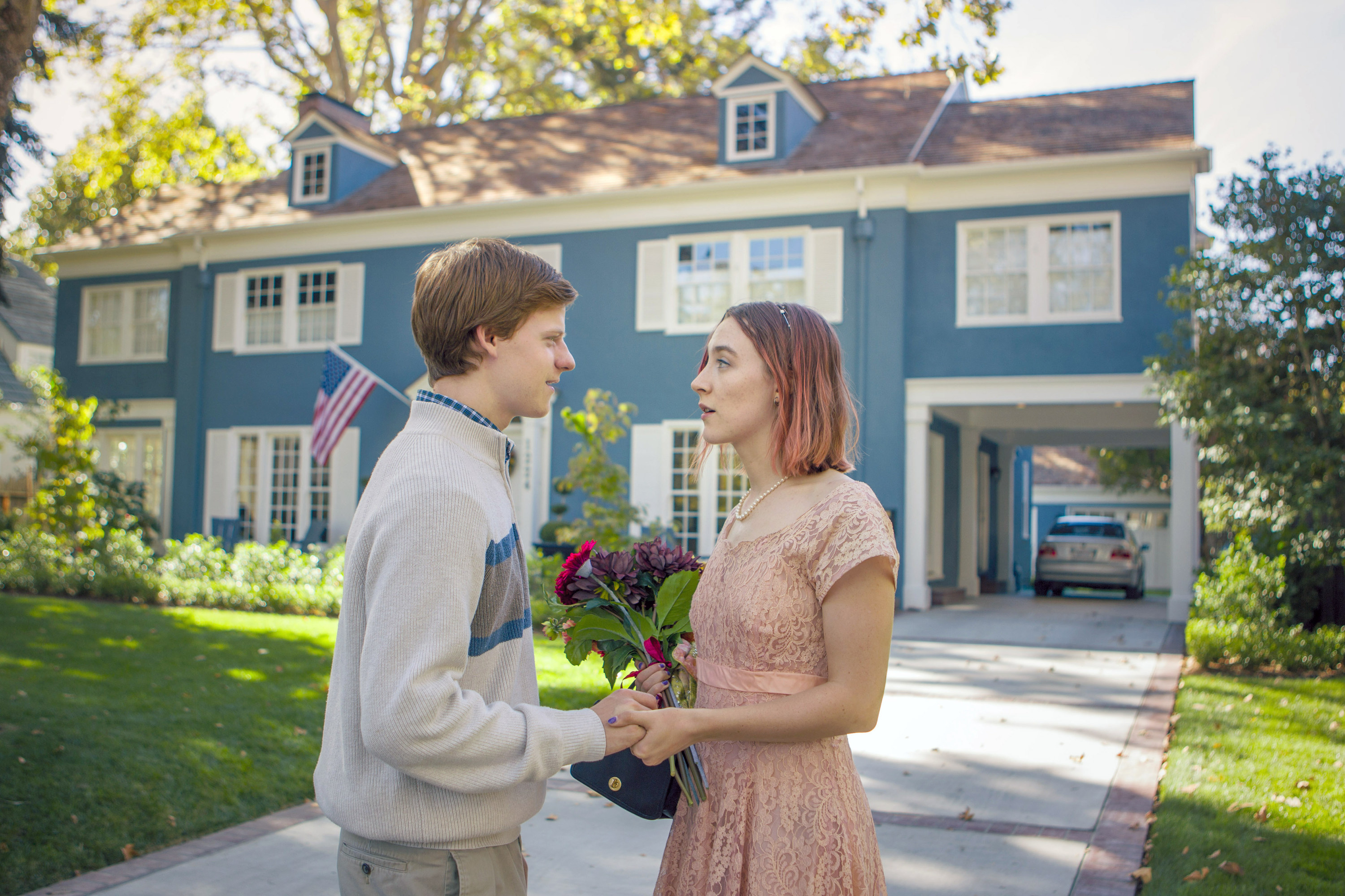 Lucas Hedges and Saoirse Ronan chat outside a gorgeous blue house