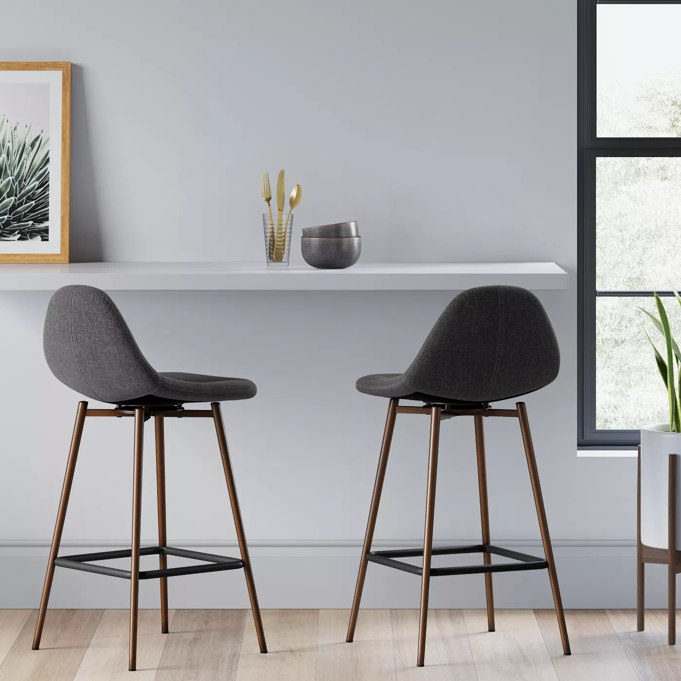 Two gray bar stools with metal legs in front of a kitchen island