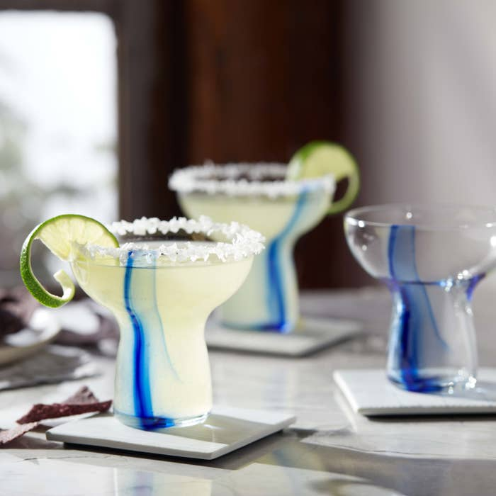three stemless margarita glasses with blue ribbons blown into the glass. Glasses are filled with margaritas with limes and salt on the rim.