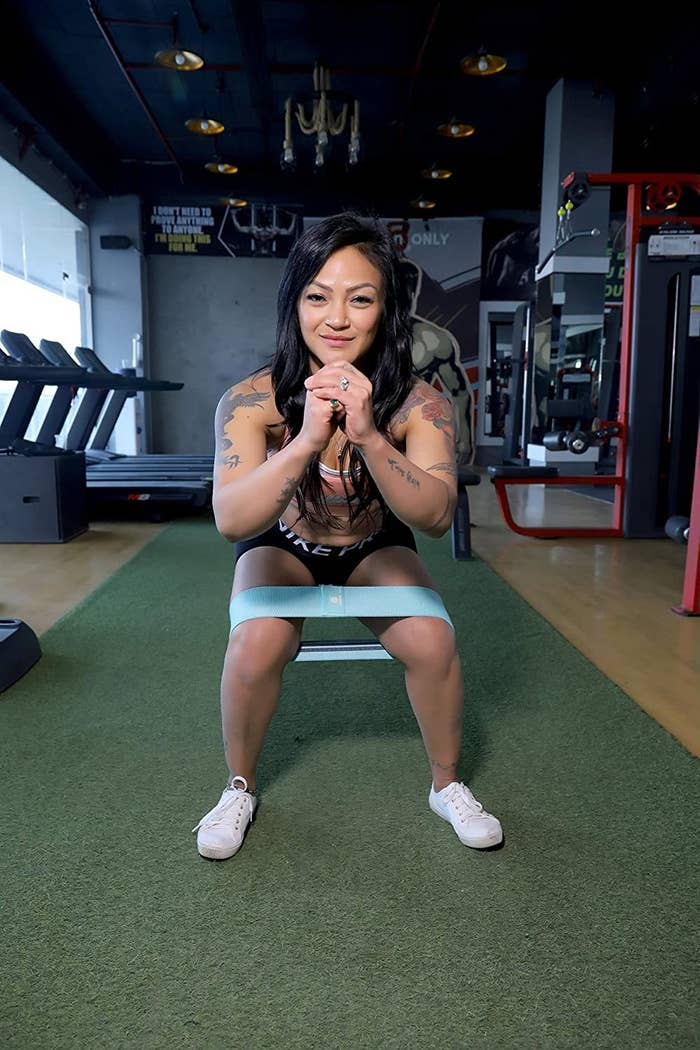A woman squatting with the resistance band on