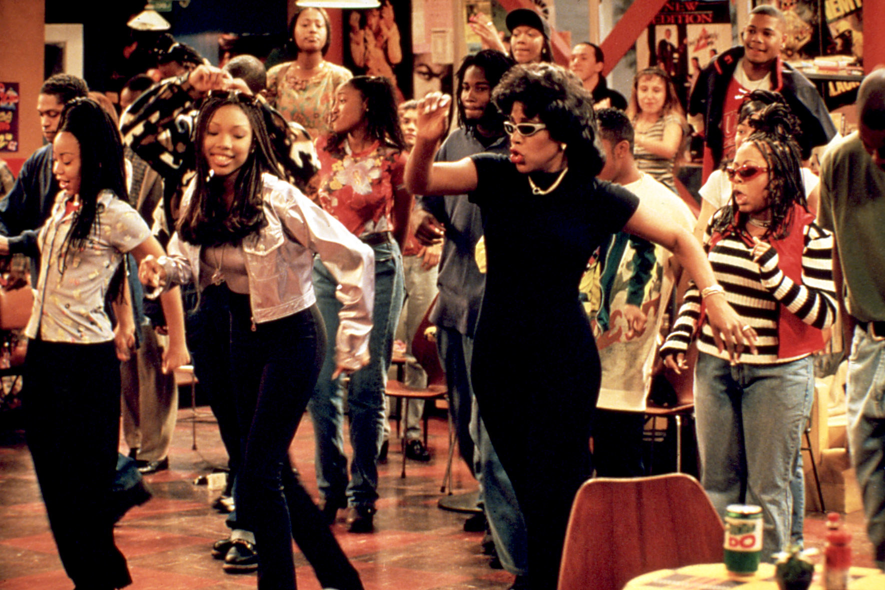 a still of Brandy Norwood as Moesha Mitchell, Sheryl Lee Ralph as Dee Mitchell and Countess Vaughn as Kim Parker dancing on the set of Moesha