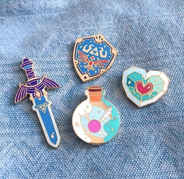 four legend of zelda pins: master sword, hyleian shield, fairy bottle, and heart piece