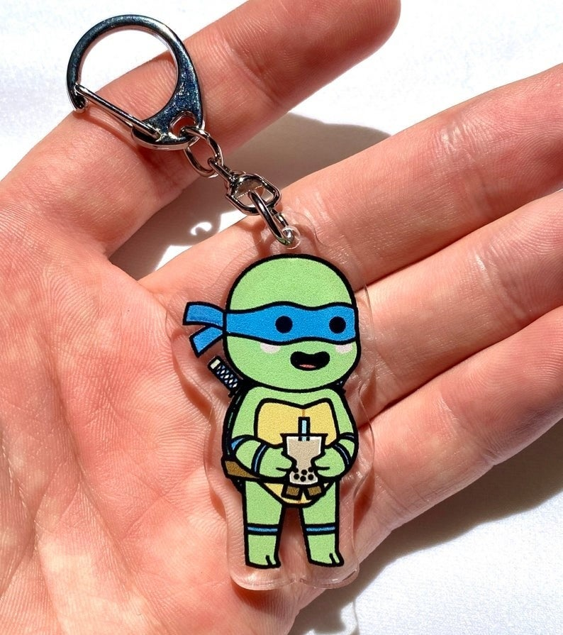 a little ninja turtle on a keychain holding a cup of bubble tea
