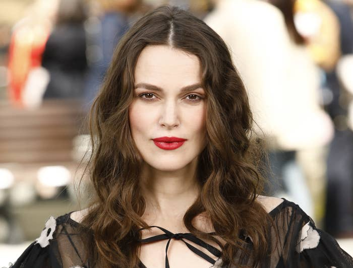 Keira wears a bold red lipstick while posing at an event
