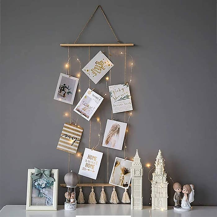 A wall hanging with attached wooden clips for hanging up pictures and notes. It's laden with fairy lights.