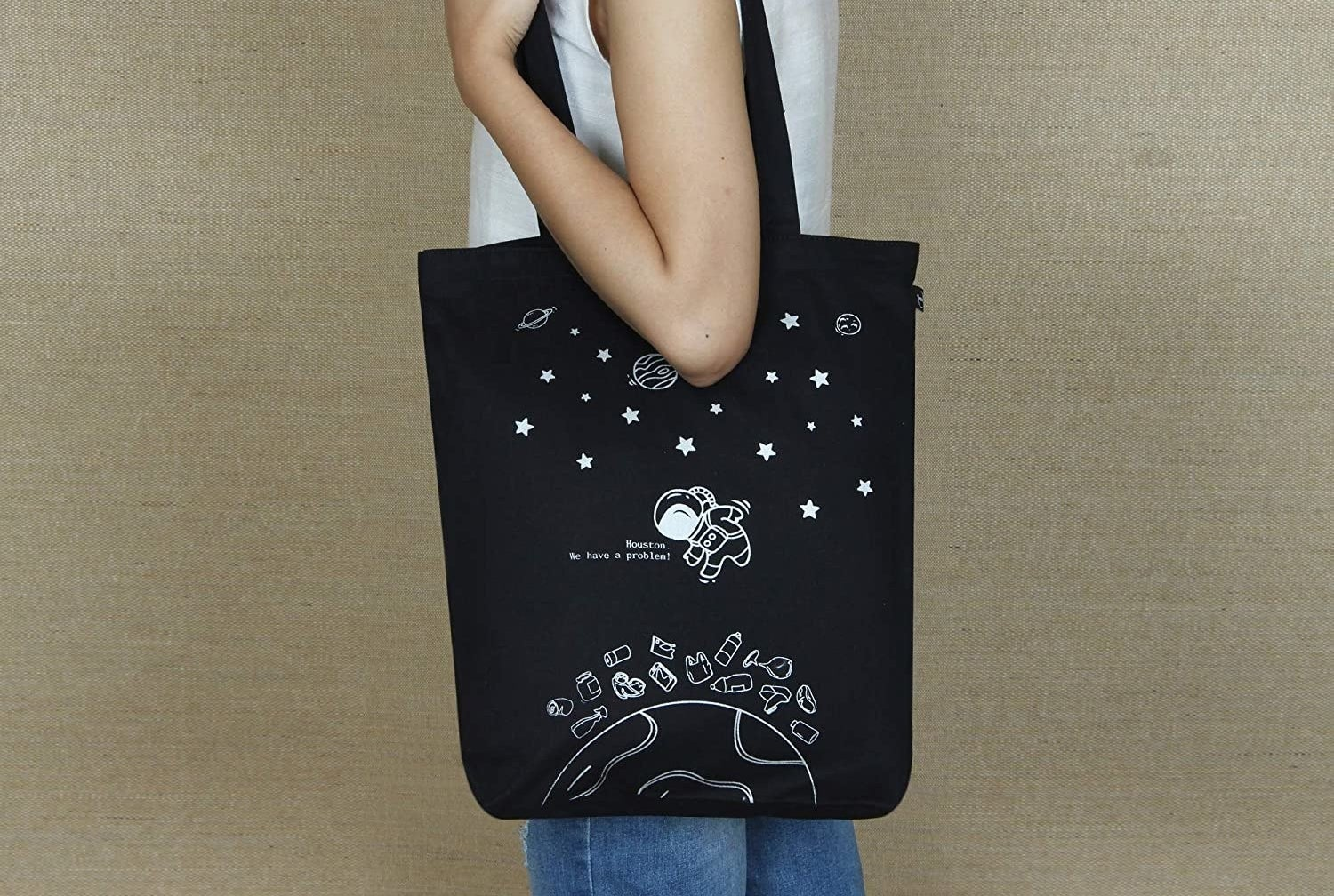 A black tote with and astronaut, stars, planets, and grocery items printed on it in white.