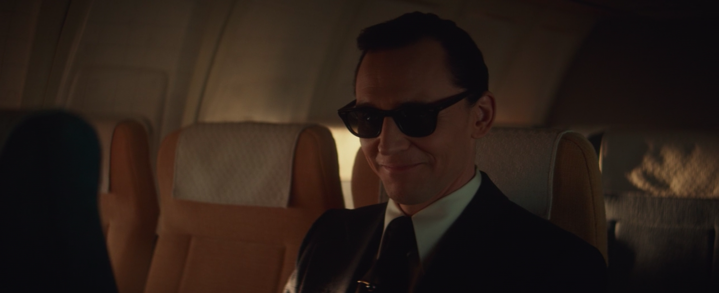 """Loki smiling with sunglasses as """"D B Cooper"""""""