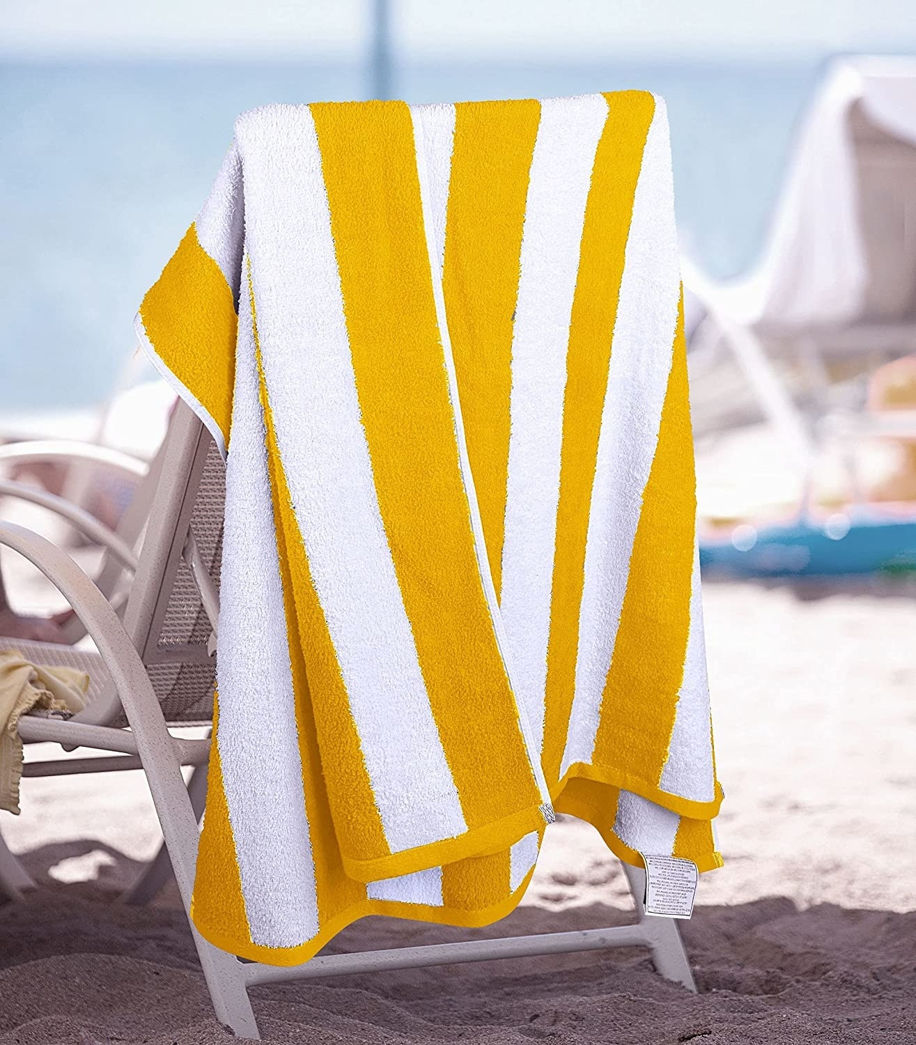 yellow beach towel hanging on the back of a chair