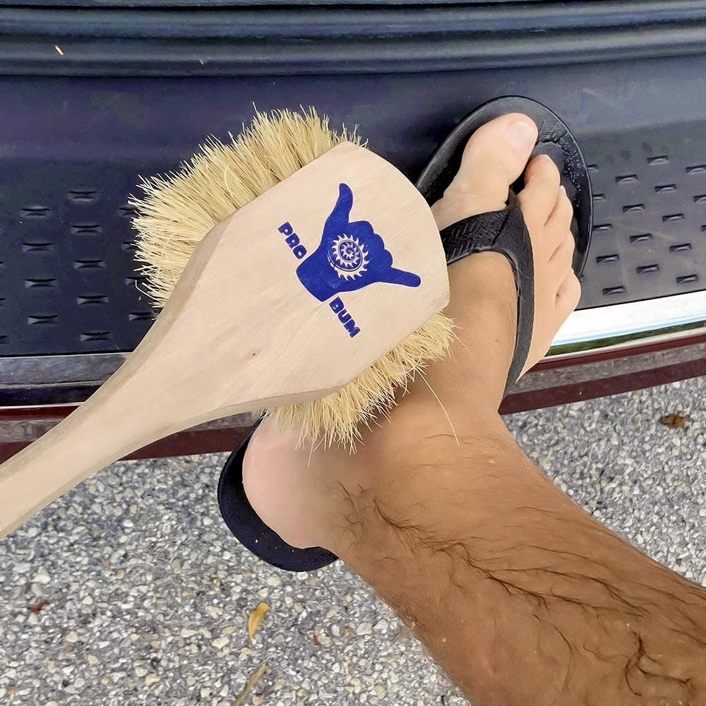 person using a pro bum brush to brush off the sand from feet