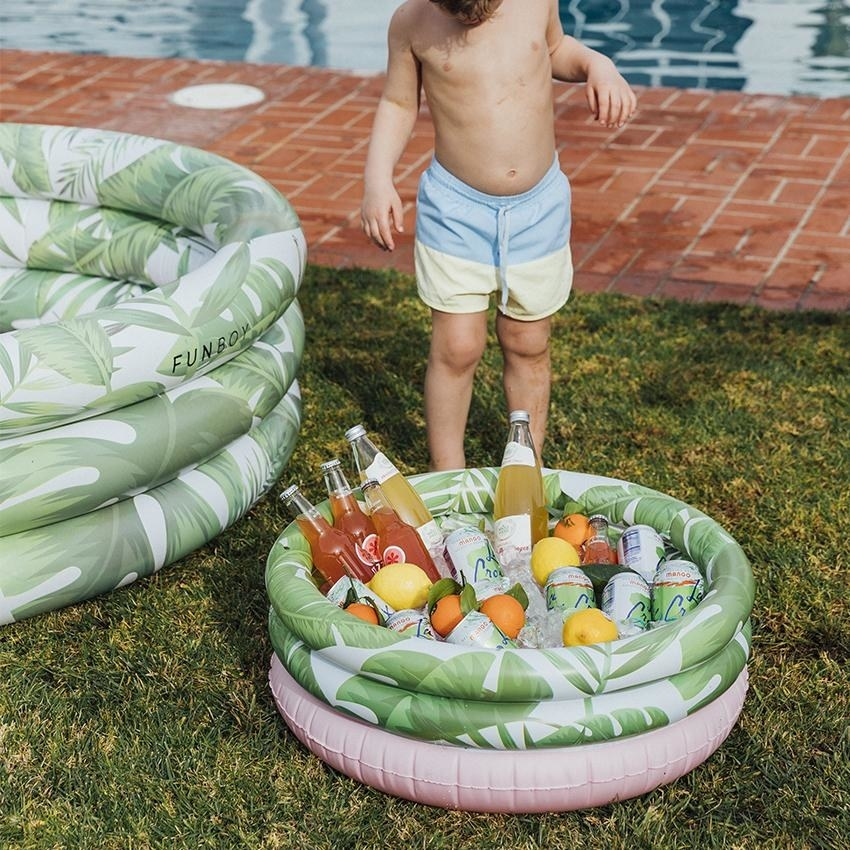 kiddie pool-shaped tropical print cooler with bottles and cans in it