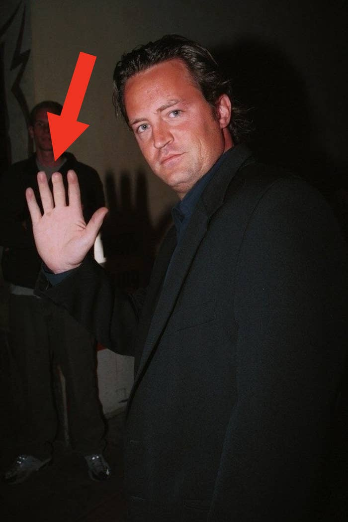 Matthew Perry with his hand raised