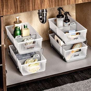 two storage towers with bath products sitting underneath a sink