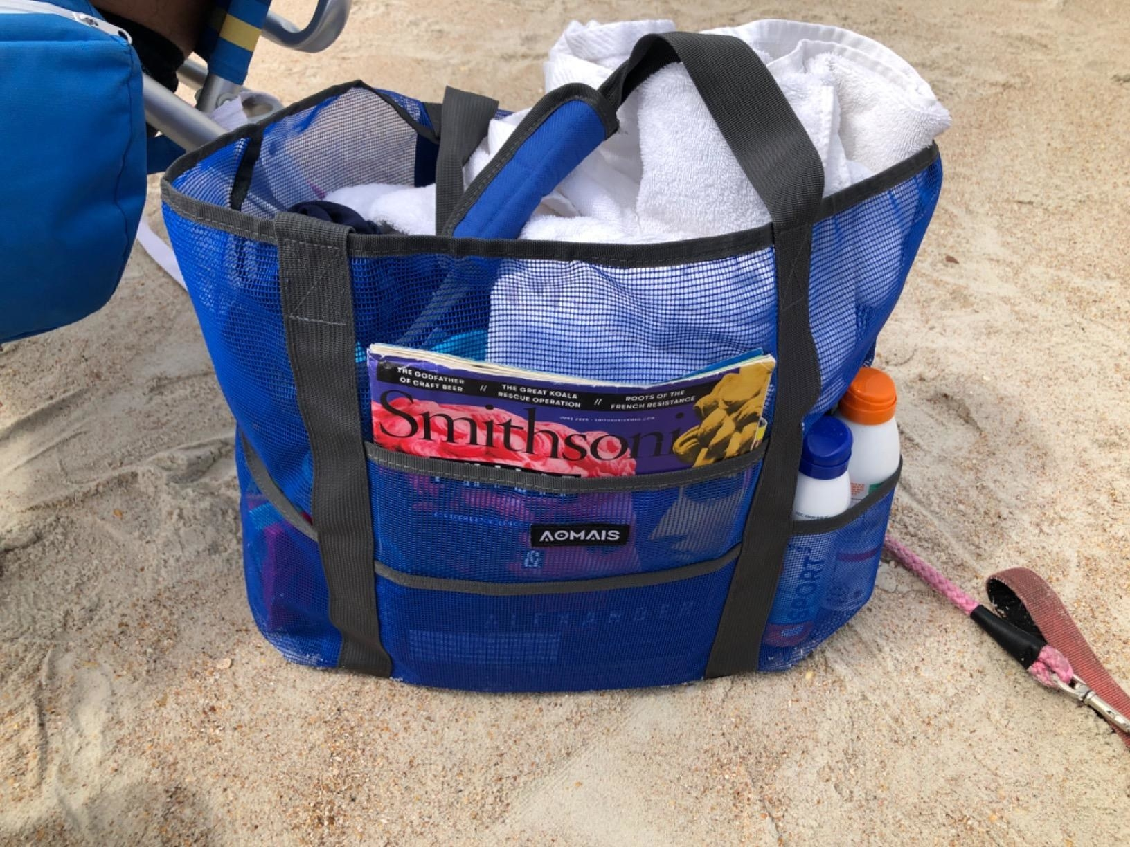 Reviewer's blue beach tote stocked with sunscreen and towels on the sand