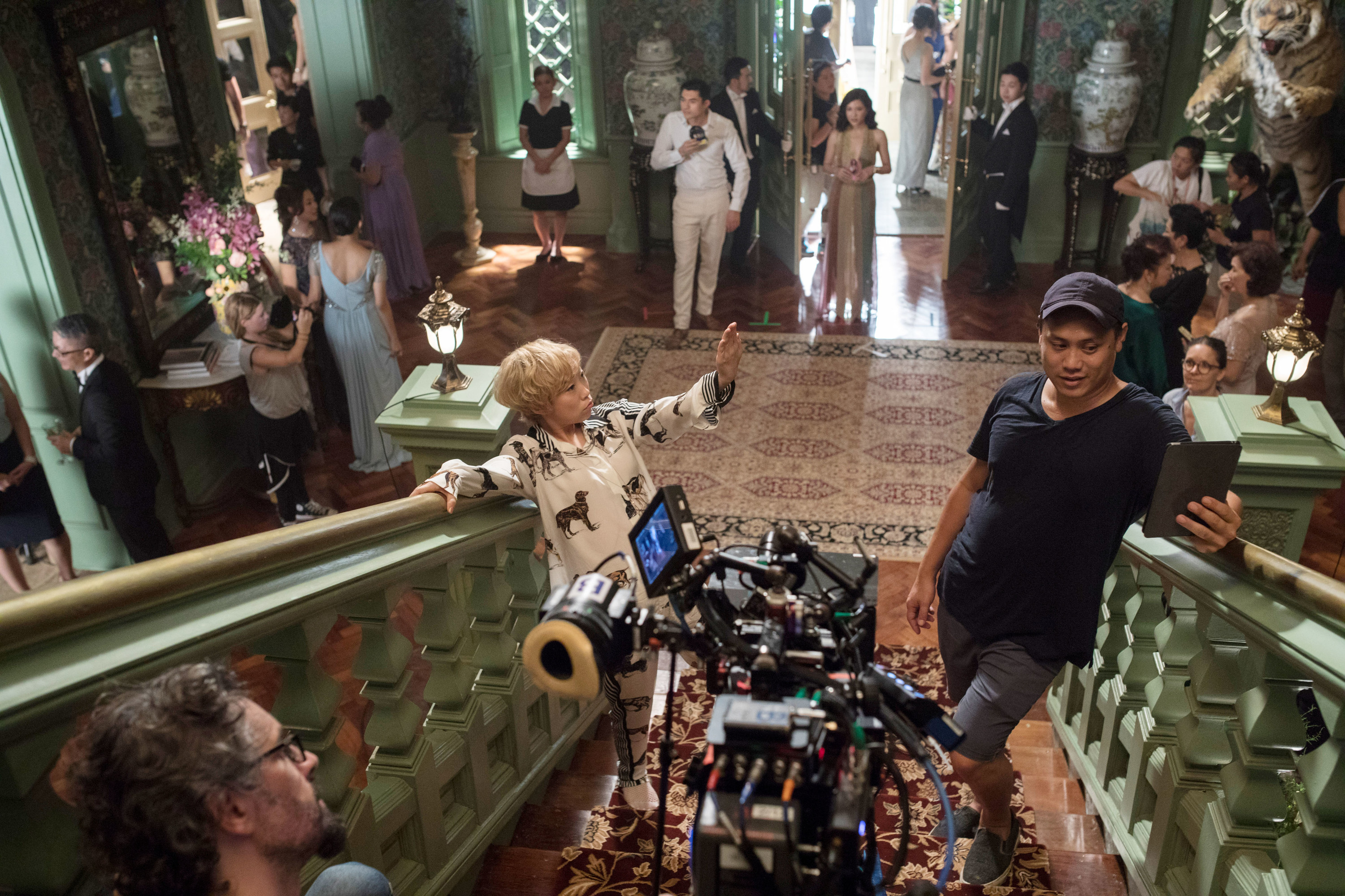"""On set of """"Crazy Rich Asians,"""" Awkwafina, director Jon M. Chu, Henry Golding, and Constance Wu prep a scene"""