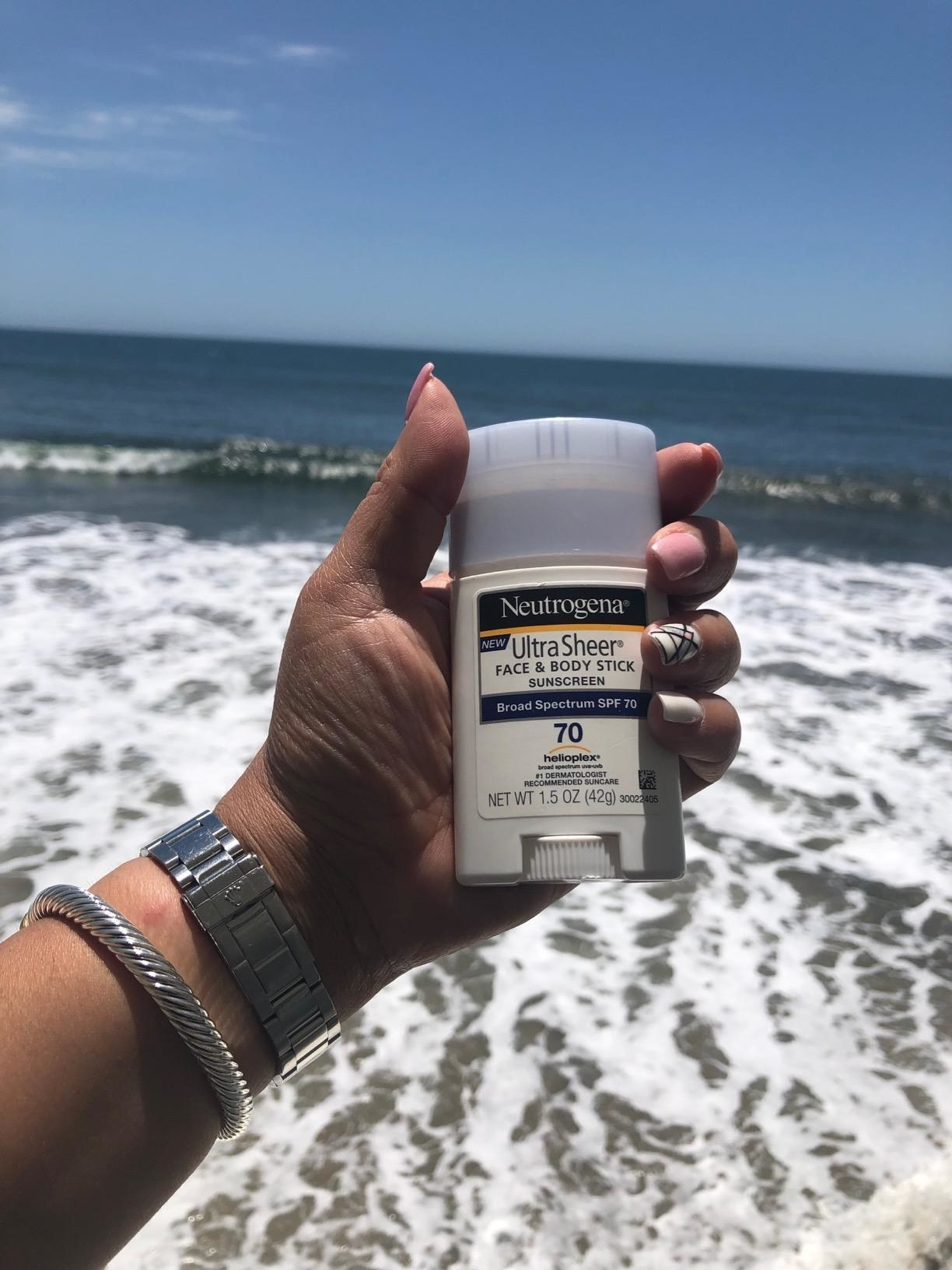 reviewer holding up a tube of neutrogena sunscreen at the beach