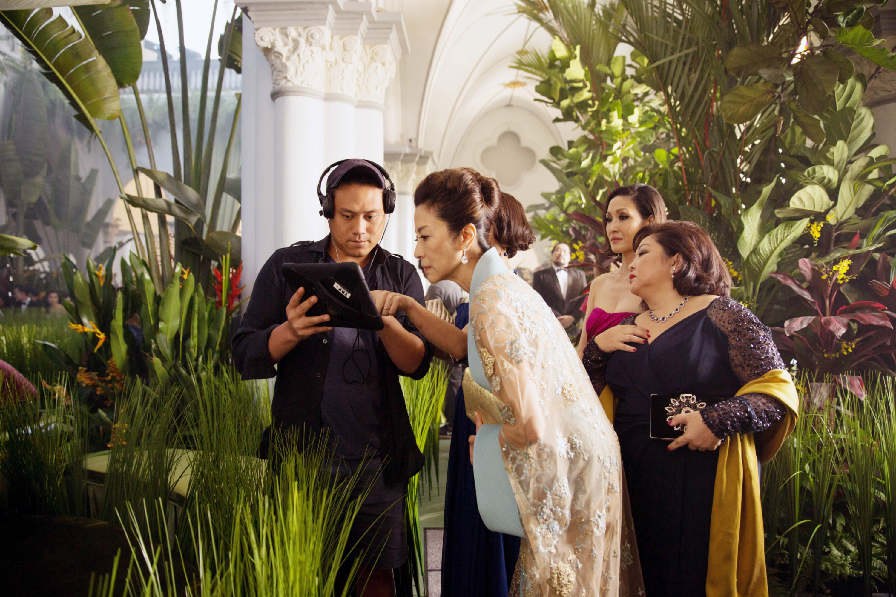 """Director Jon M. Chu, Michelle Yeoh, Amy Cheng, and Selena Tan examine a scene on set of """"Crazy Rich Asians"""""""