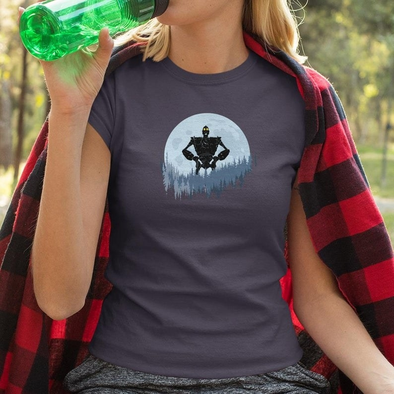 A person wearing a t-shirt with the iron giant in a forest designed on the front